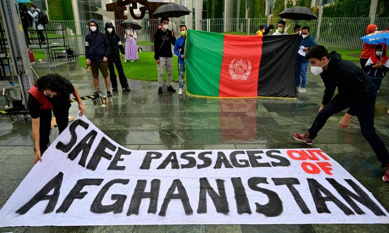 """Manifestantes exibem uma bandeira do Afeganistão e seguram uma faixa com a frase """"passagens seguras para fora do Afeganistão"""", em Berlim Foto: JOHN MACDOUGALL / AFP"""
