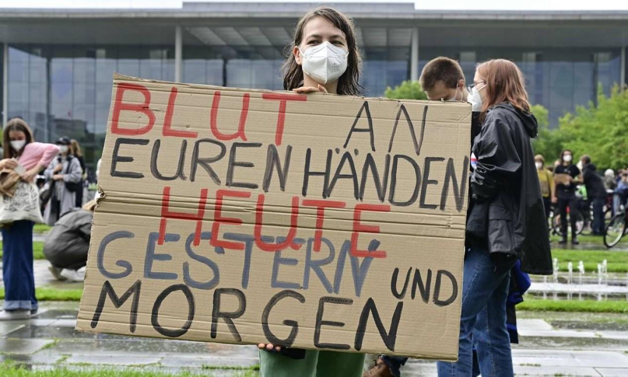 """Um manifestante exibe um cartaz com os dizeres """"Sangue nas mãos hoje, ontem e amanhã"""", em Berlim Foto: JOHN MACDOUGALL / AFP"""