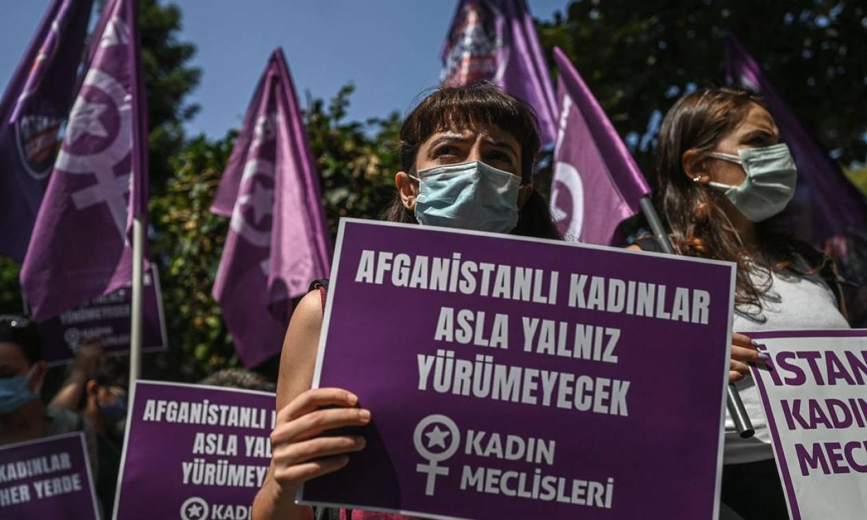 """Em Istambul, na Turquia, mulheres exibem cartazes com a frase """"Mulheres afegãs nunca caminharão sozinhas"""", em frente ao consulado do Afeganistão na capital Foto: OZAN KOSE / AFP"""