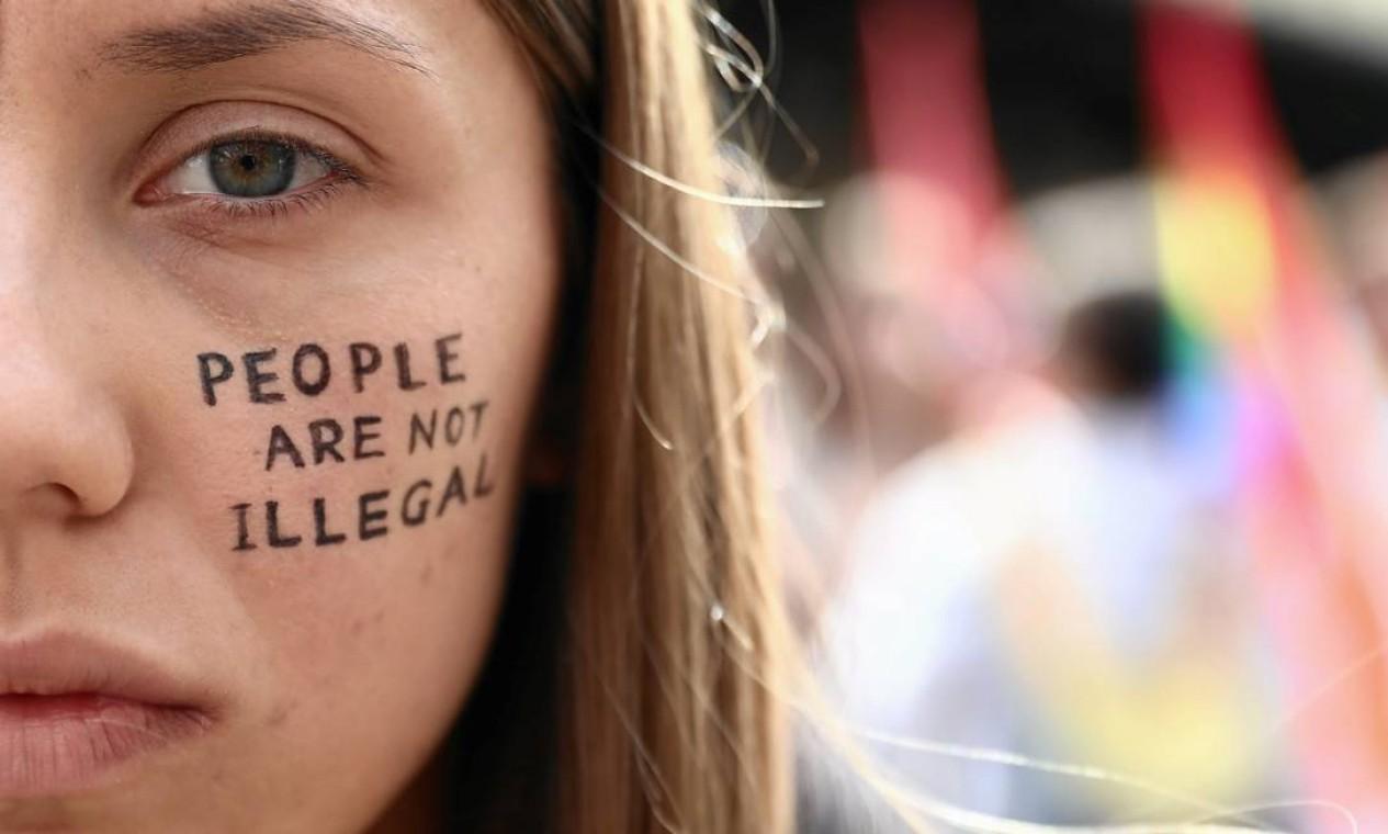 """Mulher tem pintada no rosto a mensagem """"pessoas não são ilegais"""" durante manifestação de solidariedade ao povo do Afeganistão, em Cracóvia, Polônia Foto: JAKUB PORZYCKI / Agencja Gazeta via REUTERS"""