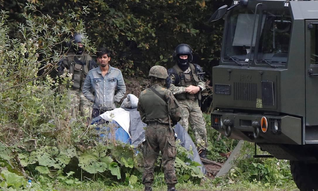 Guardas da fronteira da Polônia e da Bielorrússia perto de grupo de imigrantes na fronteira dos países Foto: Kacper Pempel / Reuters