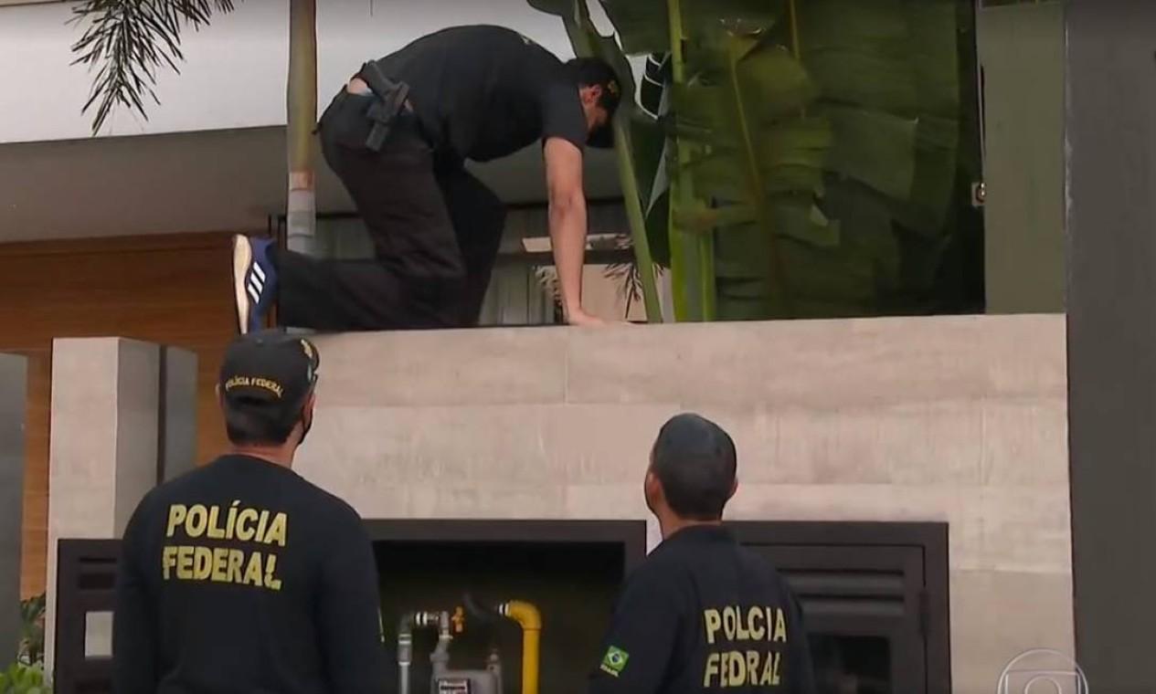 Agentes pulam para dentro da casa de Glaidson, em condomínio na Barra da tijuca, na Zona Oeste do Rio, onde Glaidson foi preso Foto: Agência O Globo