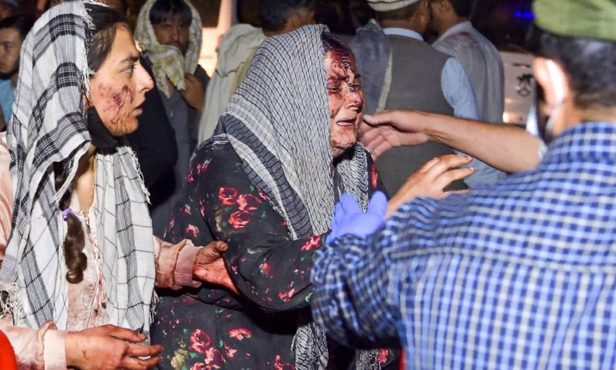 Mulher ferida no atentado do aeroporto é atendida por voluntários Foto: WAKIL KOHSAR / AFP