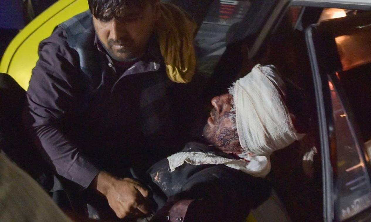 Equipe médica e carrega homem ferido para fora de um carro após duas explosões no aeroporto de Cabul Foto: WAKIL KOHSAR / AFP