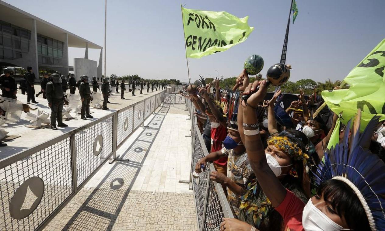 Indígenas protestam diante de uma barreira instalada em frente ao Palácio do Planalto monitorados por policiais Foto: Cristiano Mariz / Agência O Globo - 27/08/2021