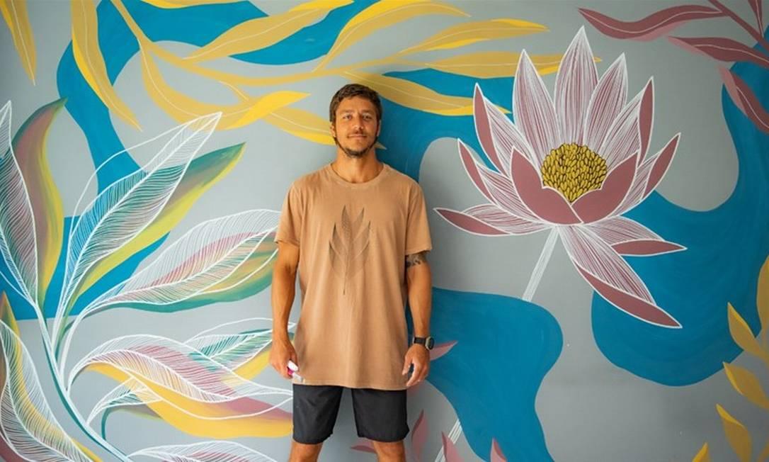 Jonas Tikerpe. O artista com uma de suas criações: elementos botânicos e formas geométricas são recorrentes em seu trabalho Foto: Divulgação