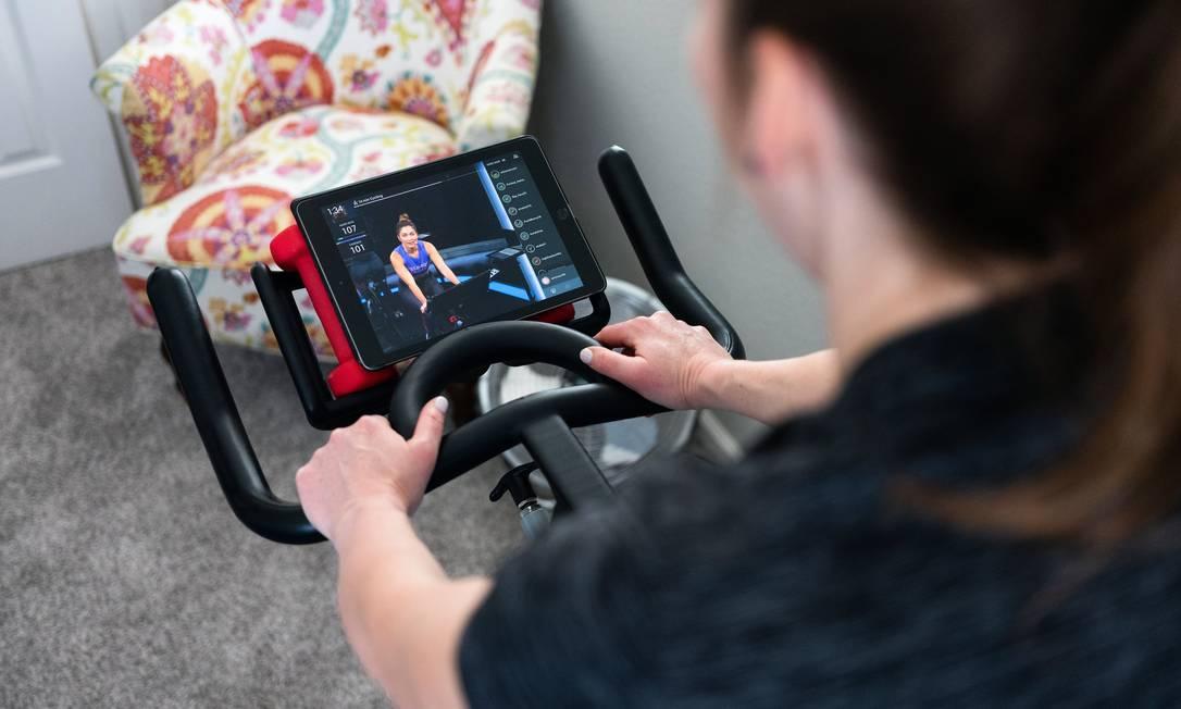 Americana faz exercícios comandados por instrutora na plataforma digital Foto: MAX WHITTAKER / NYT/27-2-2021