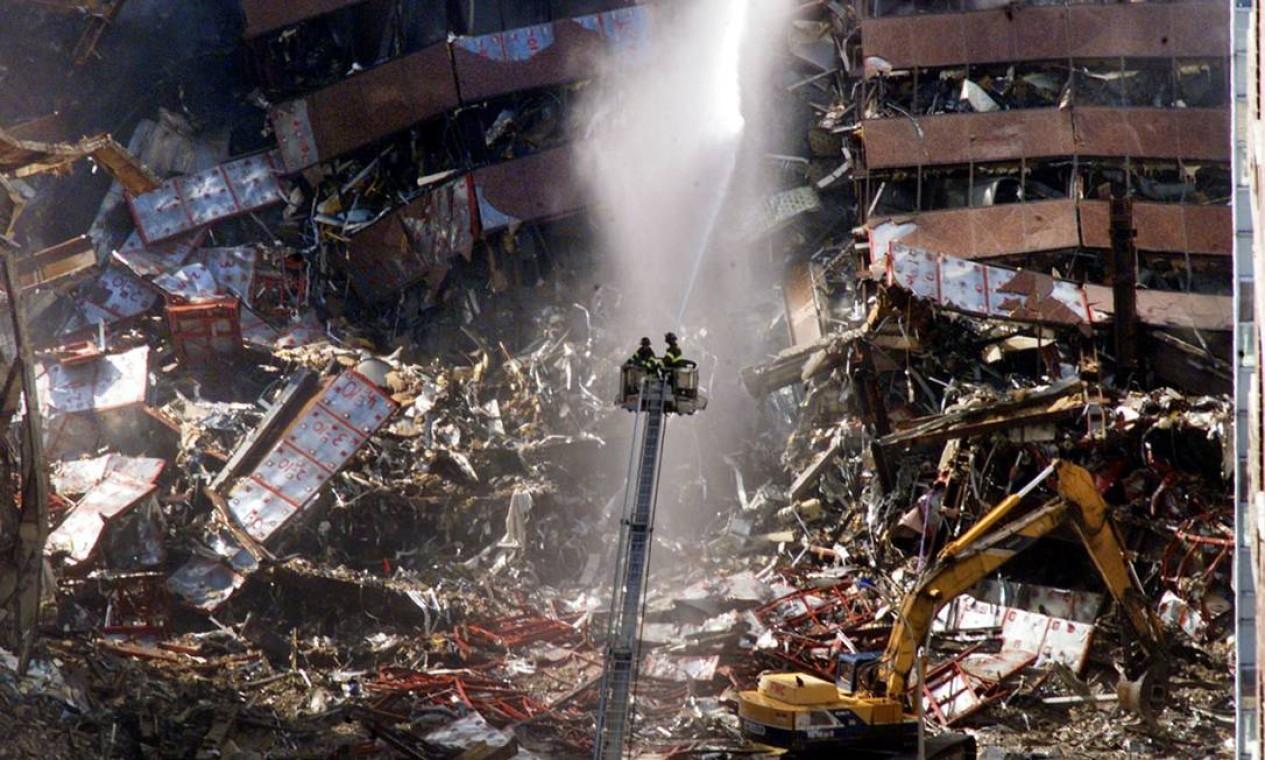 Bombeiros despejam água nos destroços do World Trade Center, no dia seguinte ao atentado Foto: Mike Segar / Reuters