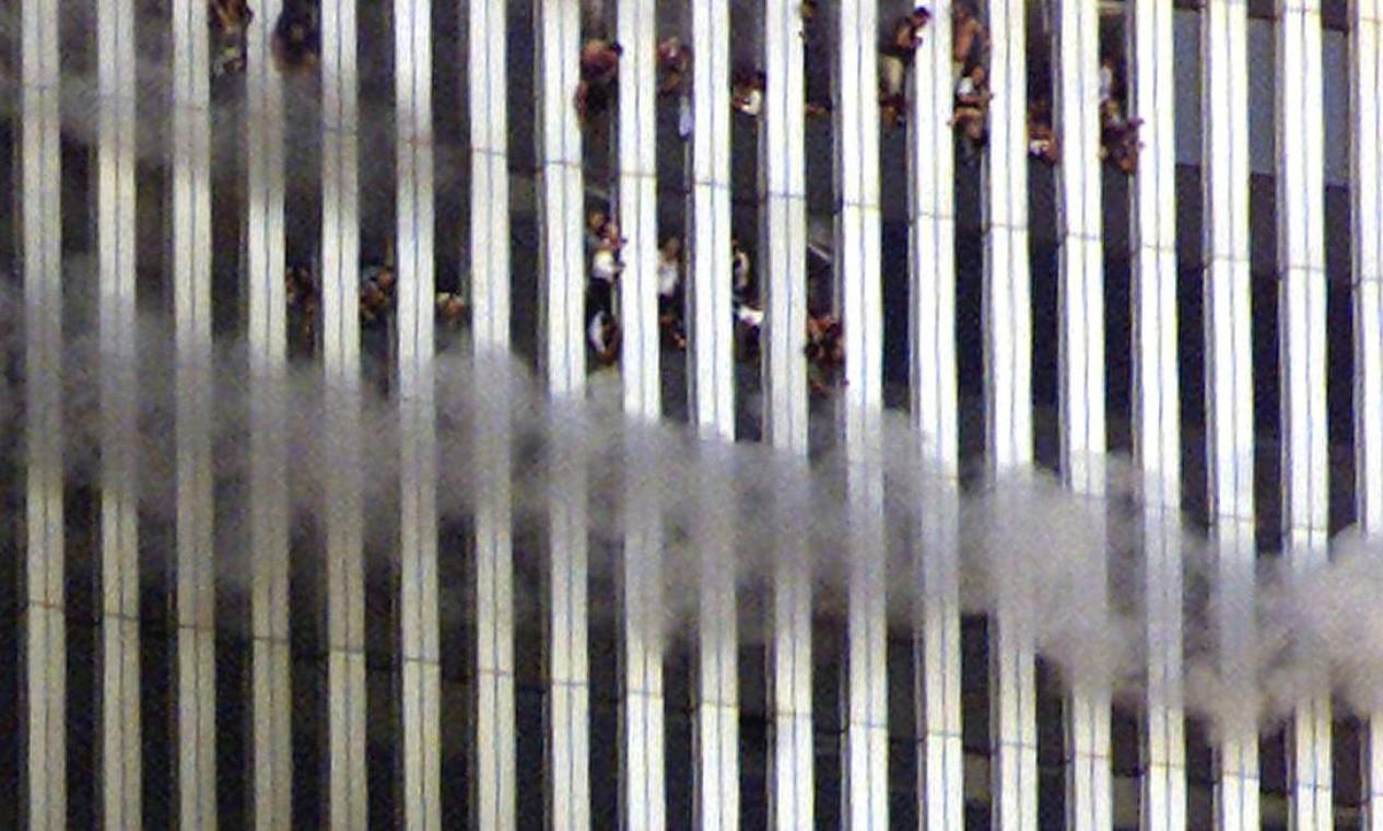 Pessoas são vistas nas janelas da torre Norte em chamas Foto: Jeff Christensen / Reuters