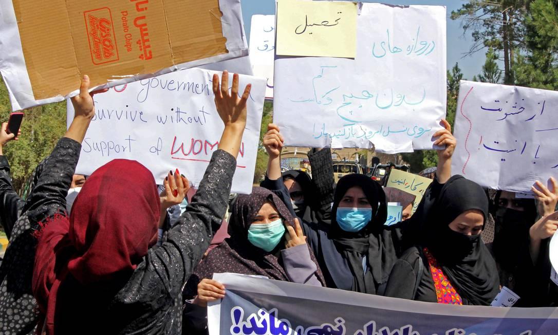 Mulheres afegãs seguram cartazes em meio a protesto por direitos em Herat, no Afeganistão Foto: - / AFP