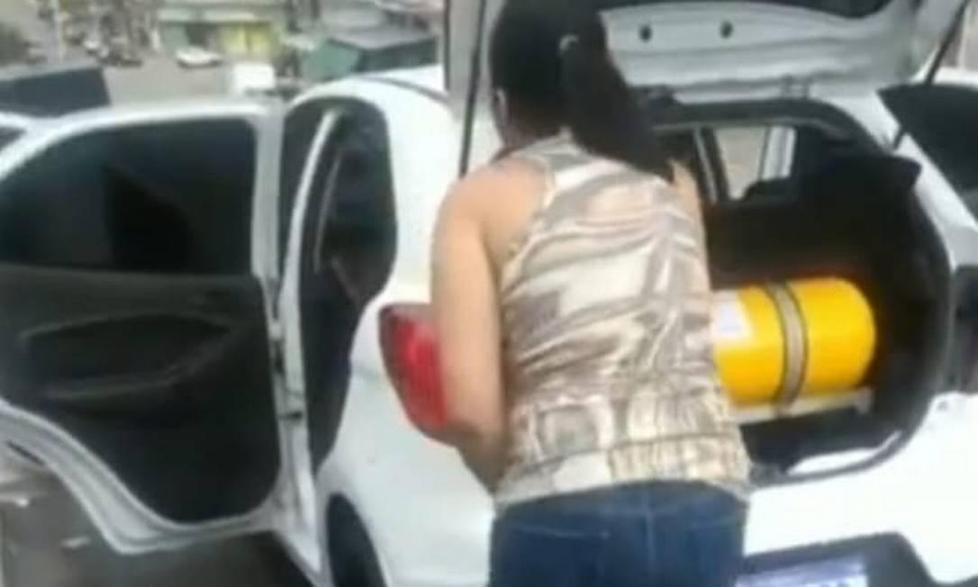 Mulher procura abrigo atrás de um carro para se proteger de um tiroteio em Mesquita Foto: Reprodução / TV Globo