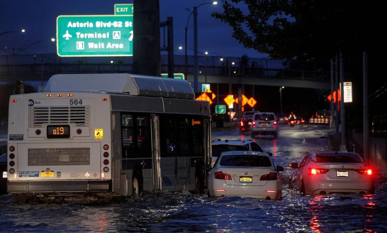 Ônibus passa por carros abandonados em uma rodovia inundada, no bairro de Queens, em Nova York Foto: BRENDAN MCDERMID / REUTERS