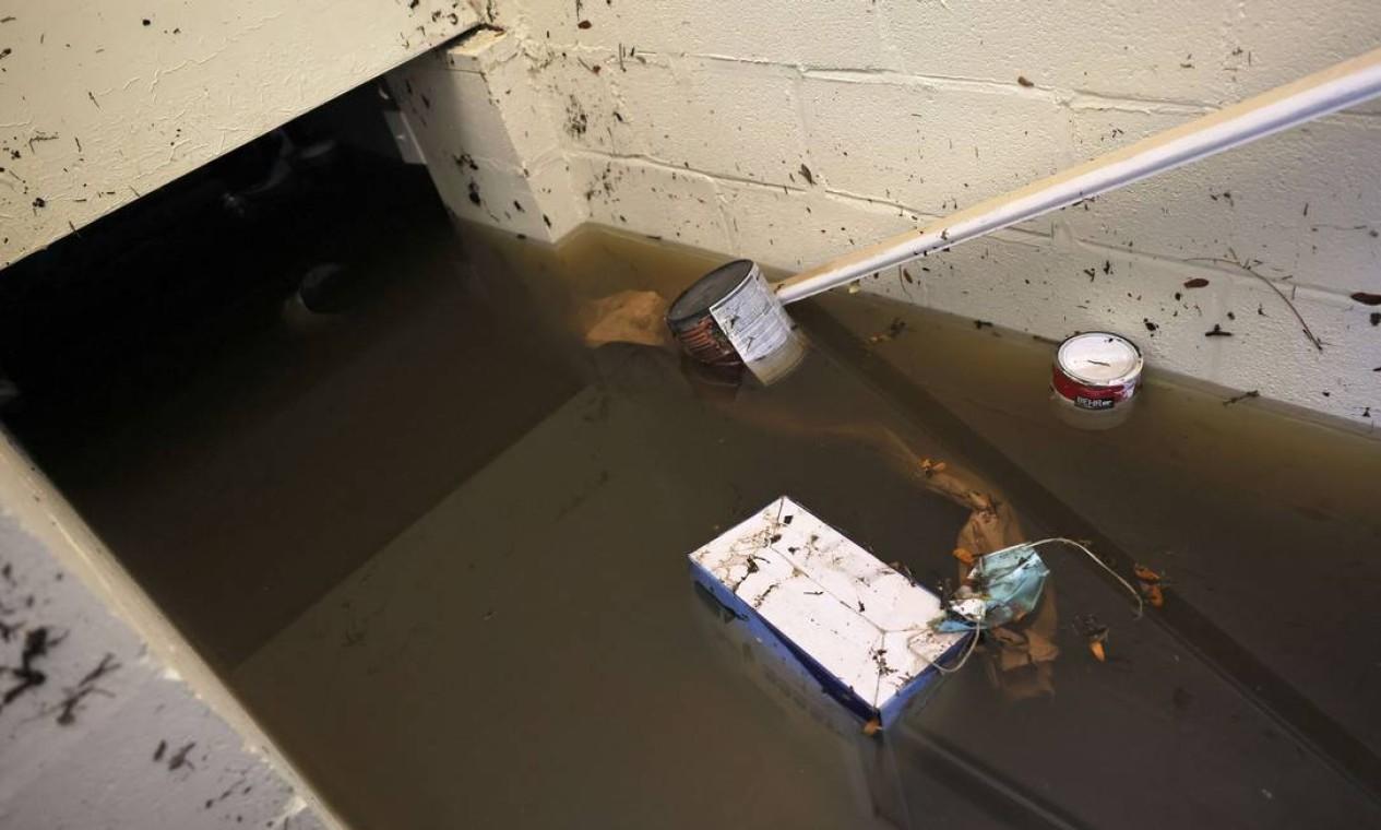 Caixa de máscaras é vista flutuando no porão inundado de uma casa em Lester Street, em Passaic City, Nova Jersey Foto: Michael M. Santiago / AFP