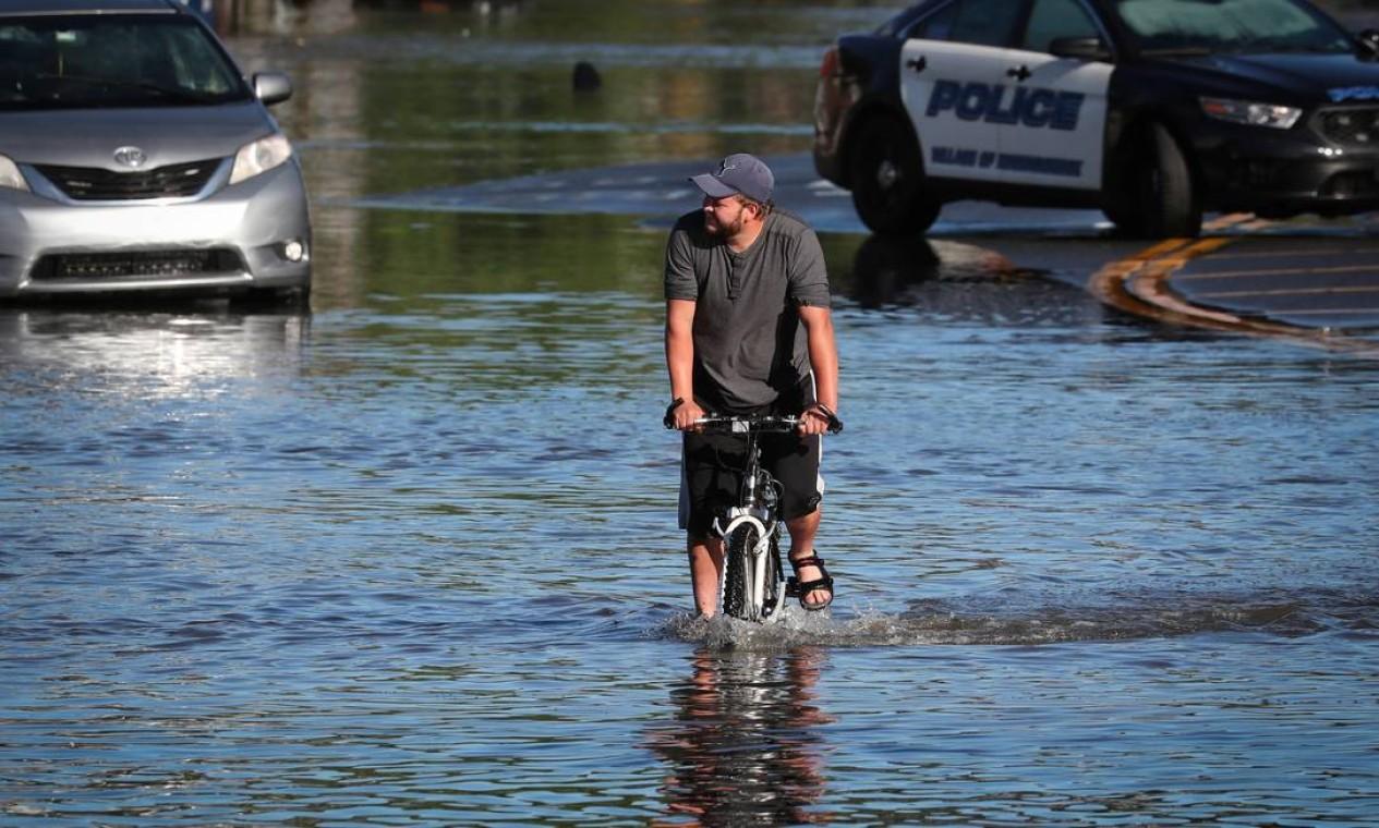 Homem anda de bicicleta pelas águas da enchente enquanto moradores deixam suas casas depois que os restos da tempestade tropical Ida provocou chuva torrencial, enchentes e tornados para partes do nordeste em Mamaroneck, Nova York Foto: MIKE SEGAR / REUTERS