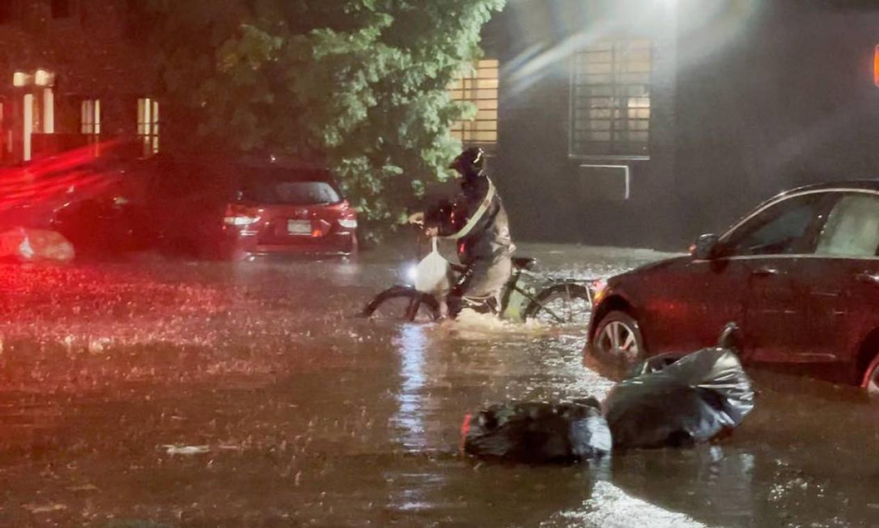 Homem empurra uma bicicleta em uma rua inundada de Nova York Foto: JOHNNY MILLER / UNEQUAL SCENES / via REUTERS