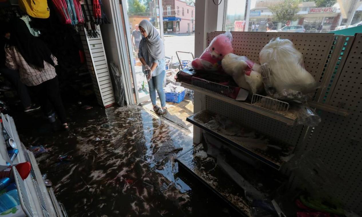 Trabalhador olha para a loja danificada pela enchente em Mamaroneck, Nova York Foto: MIKE SEGAR / REUTERS