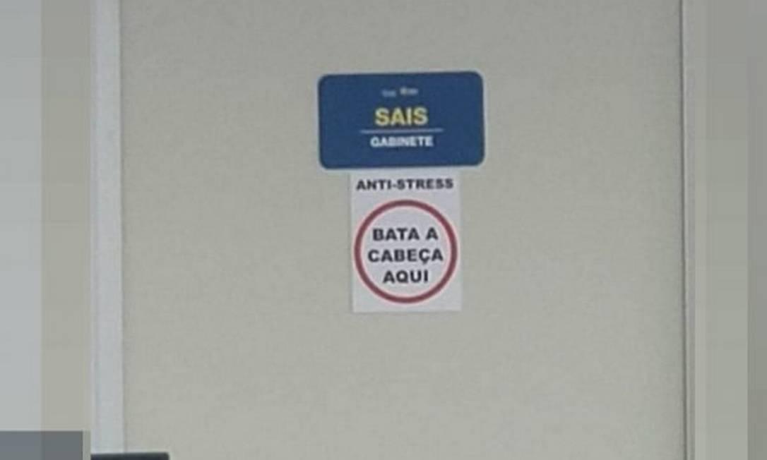 Cartaz fixado em porta de gabinete da Secretaria de Saúde do DF: 'Bata a cabeça aqui' Foto: Reprodução
