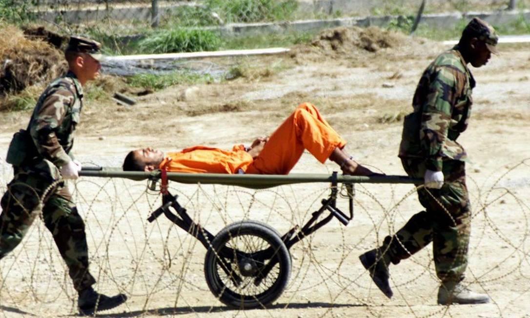 Militares americanos levam preso de Guantánamo, em Cuba, para ser interrogado; governo Bush criou a definição de 'combatente inimigo ilegal' para evitar as Convenções de Genebra Foto: Marc Serota / AFP/2-2-2002
