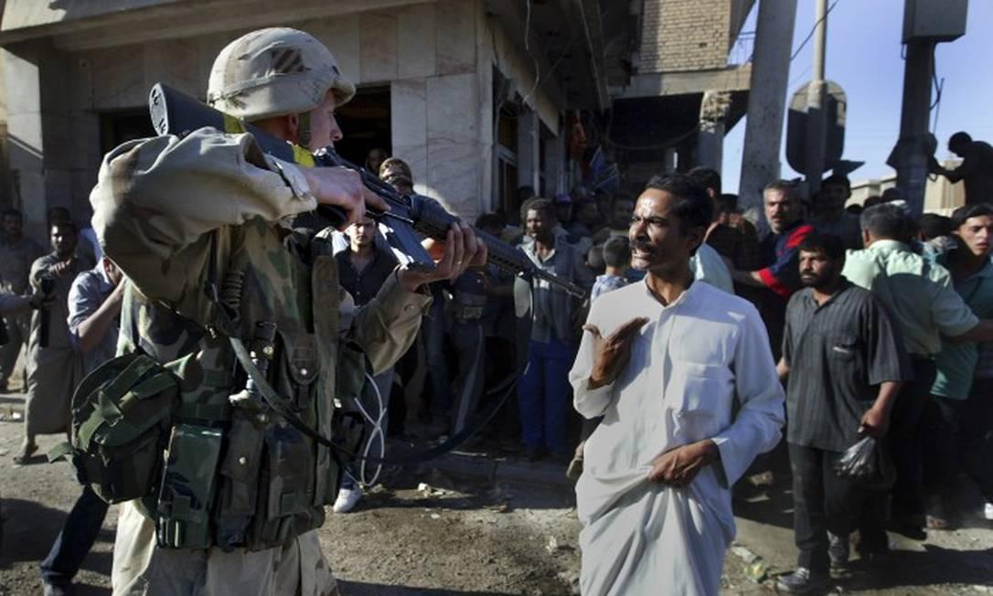 Dois meses após invasão do Iraque, soldado americano usa arma para mandar que civis se afastem de local de explosão em Bagdá Foto: TYLER HICKS / NYT/1-5-2003
