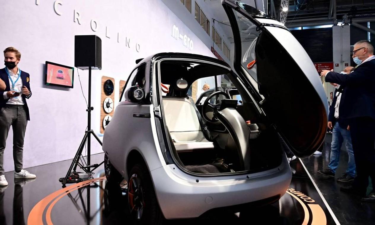 """Visitantes da feira inspecionam o carro elétrico """"bolha"""", o Microlino 2.0 Foto: TOBIAS SCHWARZ/AFP"""