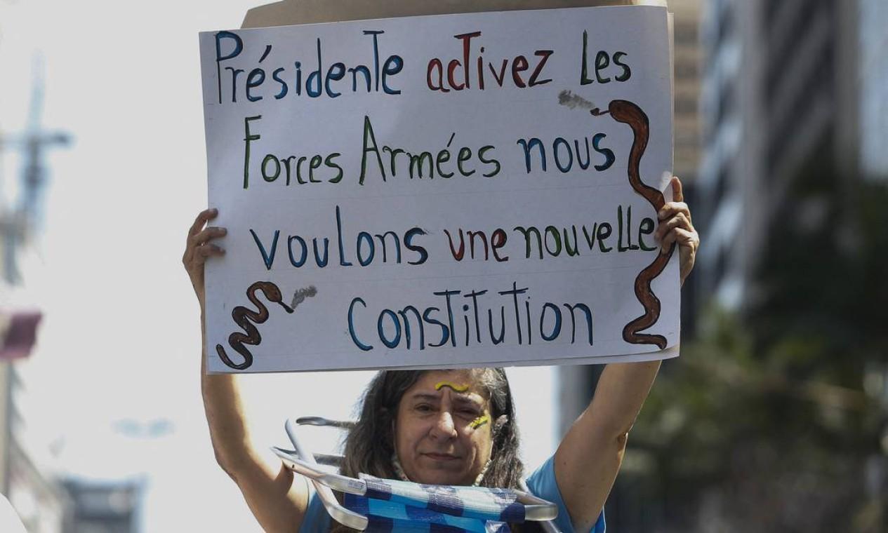 """""""Presidente, ative as forças armadas, queremos uma nova Constituição"""", diz cartaz, em francês, de manifestante na Avenida Paulista, em São Paulo Foto: MIGUEL SCHINCARIOL / AFP"""