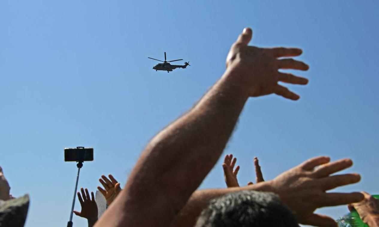 Apoiadores acenam para Bolsonaro, a bordo de helicóptero da Força Aérea Brasileira, em Brasília Foto: CARL DE SOUZA / AFP