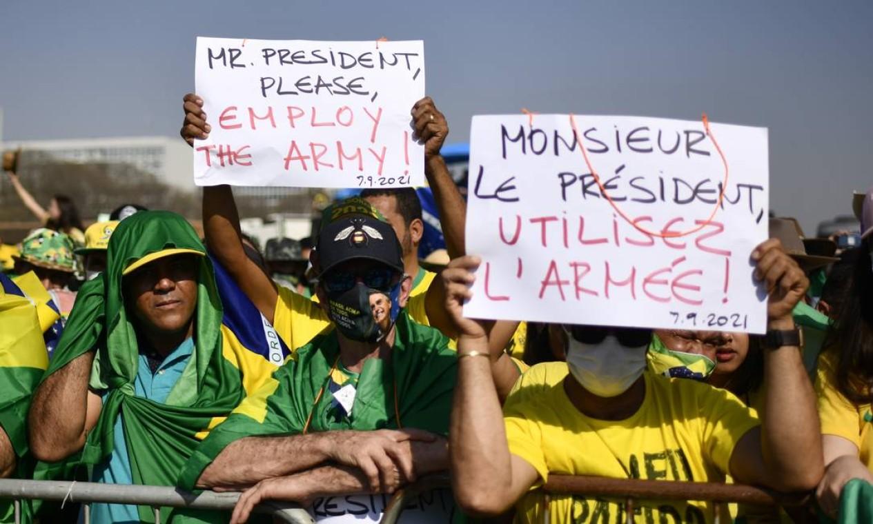 """Apoiadores do presidente Bolsonaro seguram cartazes com a mensagem: """"Senhor presidente, por favor, use as forças armadas"""", em inglês e francês Foto: Mateus Bonomi / Agência O Globo"""