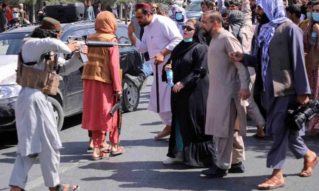 Integrante do Talibã aponta sua arma para manifestantes em um protesto nos arredores da embaixada do Paquistão, em Cabul Foto: STRINGER / REUTERS