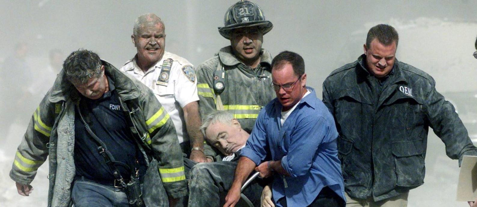 Equipes de resgate do Corpo de Bombeiros de Nova York carregam o corpo do reverendo Mychal Judge dos destroços do World Trade Center Foto: SHANNON STAPLETON / REUTERS/11-9-2001