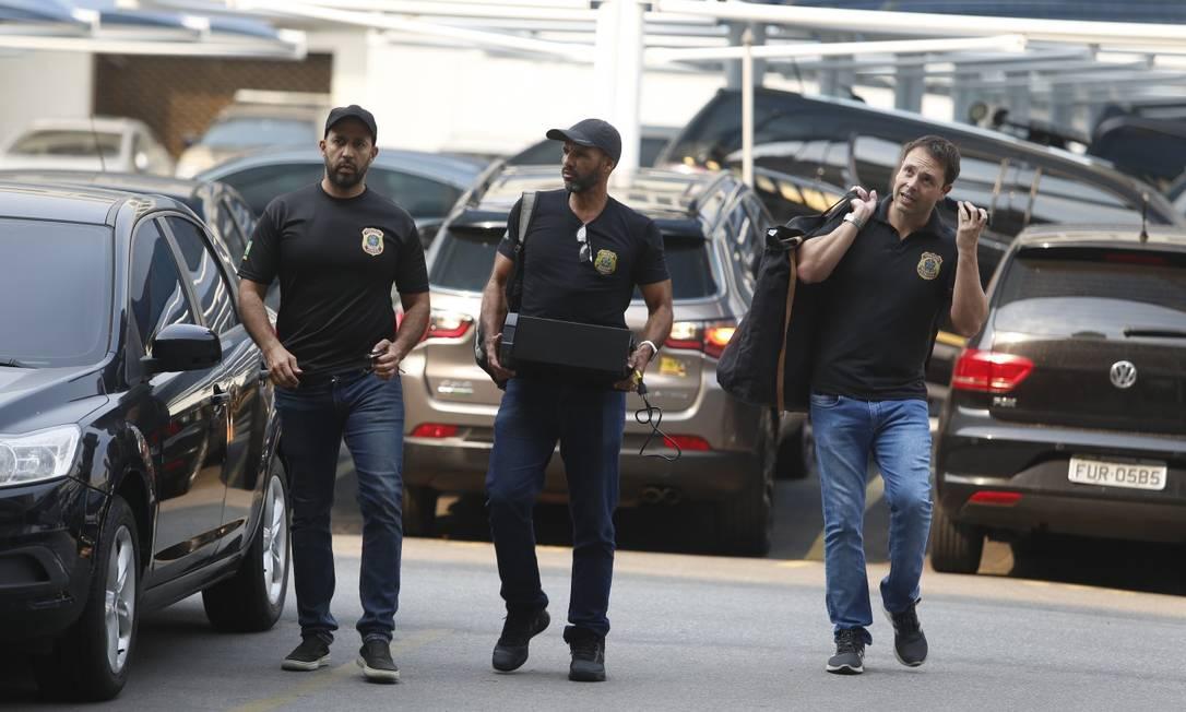 Policiais federais chegam com documentos apreendidos durante a segunda fase da Operação Kryptos Foto: Fabiano Rocha / Agência O Globo