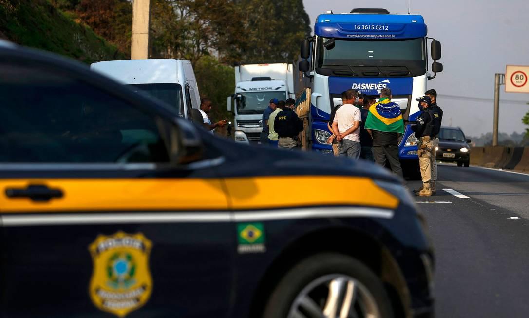 Polícia Rodoviária Federal conversa com caminhoneiros que bloqueiam a rodovia Regis Bittencourt (BR-116), a 30 km ao sul de São Paulo Foto: Miguel Schincariol / AFP
