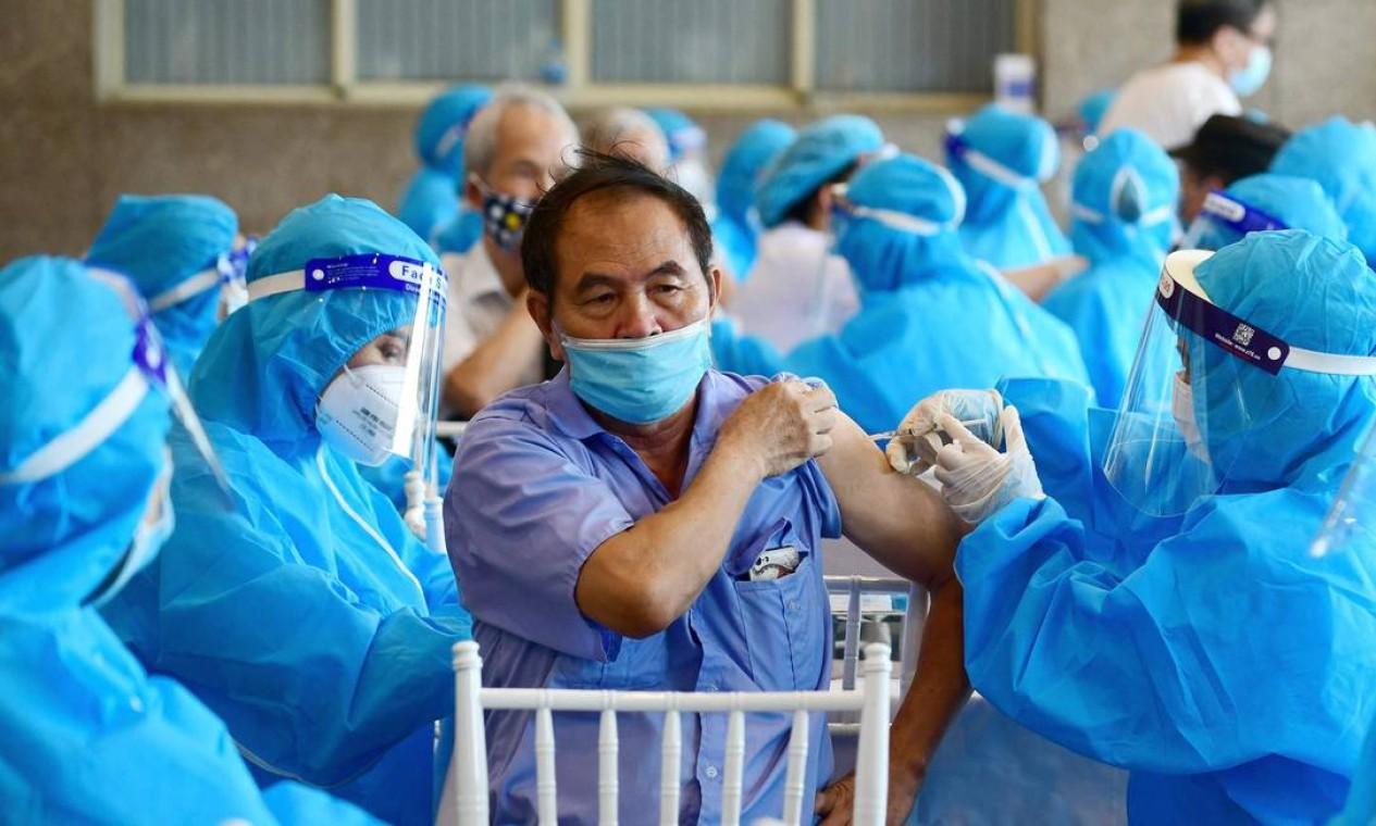 Homem recebe vacina contra Covid-19 em Hanói, Vietnã Foto: NHAC NGUYEN / AFP