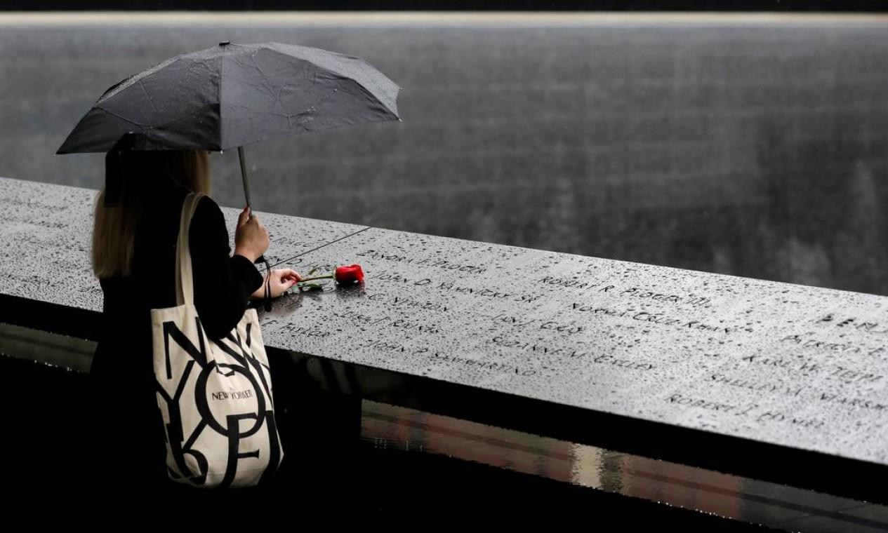 Sob chuva, mulher deixa rosa vermelha sobre memórial do 11 de setembro, em Manhattan, Nova York, Estados Unidos Foto: ANDREW KELLY / REUTERS