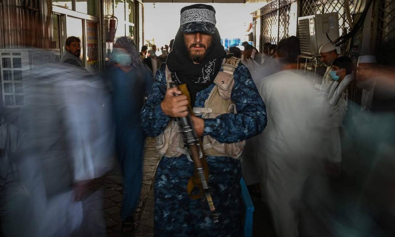 Guerrilheiro talibã é fotgrafado em meio à agitação do centro de Cabul, próximo a casas de câmbio da capital afegã Foto: AAMIR QURESHI / AFP