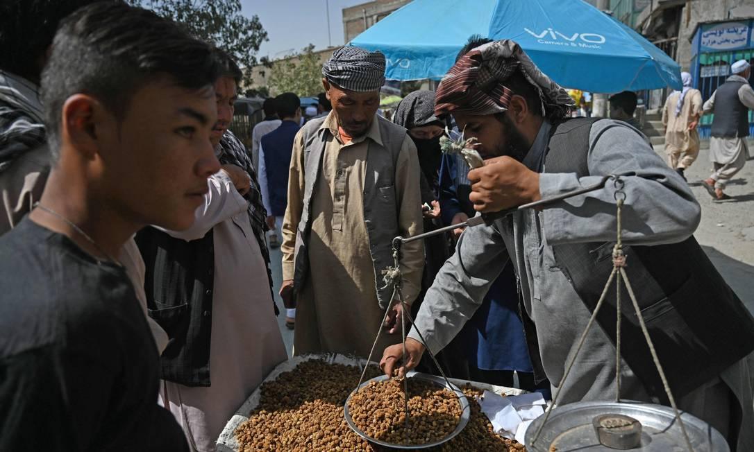 Membros da comunidade Hazara compram amora seca em mercado nos arredores de Cabul, Afeganistão Foto: AAMIR QURESHI / AFP/10-09-2021