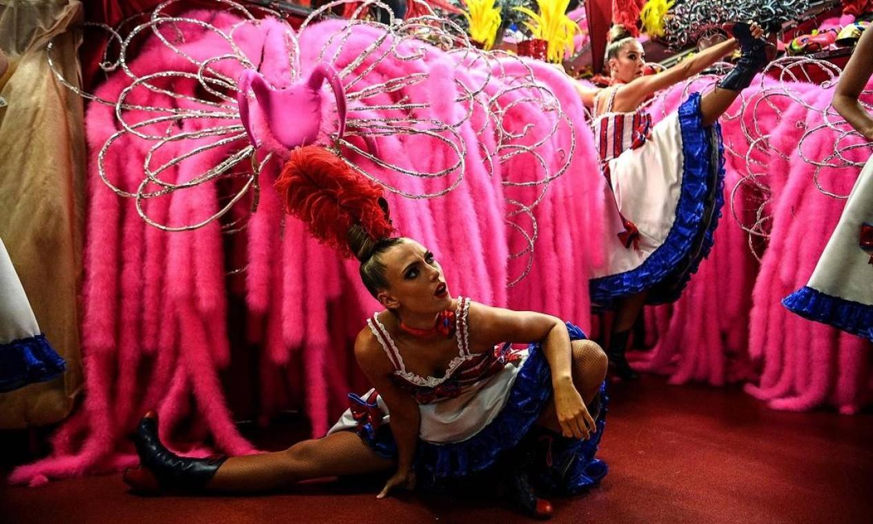 Dançarinas se alongam antes de subirem ao palco do Moulin Rouge, num dos ensaios que antecederam a reabertura do teatro em Paris, após 18 meses Foto: CHRISTOPHE ARCHAMBAULT / AFP