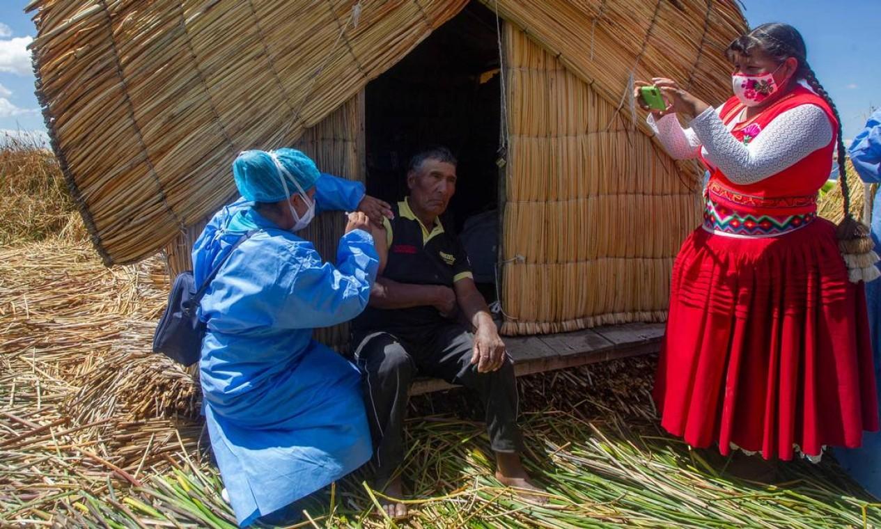 Trabalhador do Ministério da Saúde peruano vacina residente local contra Covid-19 ao lado da ex-prefeita da ilha de Uros, gerente intercultural Rita Subana, durante programa para imunizar a população vulnerável na ilha flutuante de Uros no lago Titicaca, Peru Foto: CARLOS MAMANI / AFP