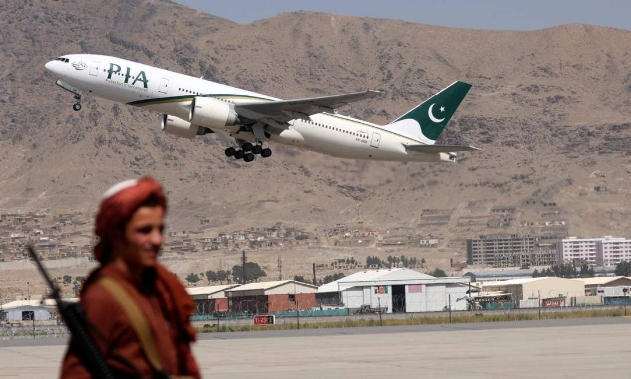 Talibã fica de guarda enquanto um avião da Pakistan International Airlines, o primeiro vôo comercial internacional a pousar desde que o Taleban retomou o poder no mês passado, decola com passageiros a bordo no aeroporto de Cabul Foto: KARIM SAHIB / AFP
