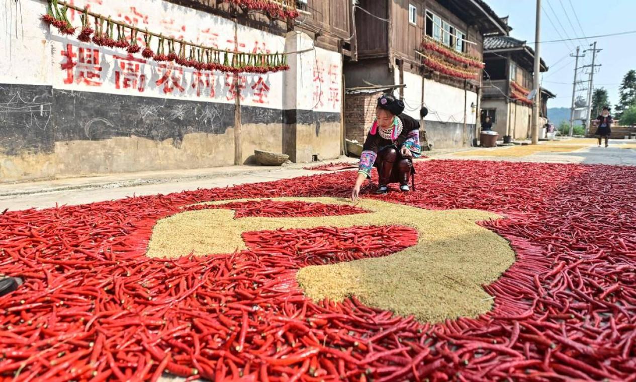 Fazendeiro cria uma bandeira do Partido Comunista Chinês com grãos e pimentão vermelho enquanto outros homens secam seus produtos colhidos em Congjiang, na província de Guizhou, no sudoeste da China Foto: STR / AFP