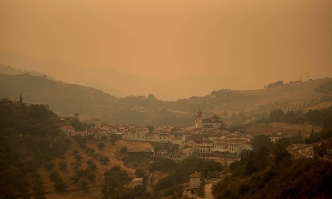 A fumaça toma o céu do vilarejo de Atajate enquanto as chamas se espalham pela Sierra Bermeja Foto: JORGE GUERRERO / AFP