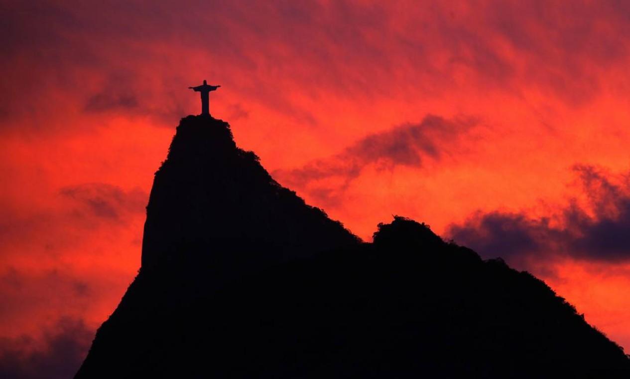 Silhueta do Corcovado, com o Cristo Redentor no topo. é vista em contraste com céu avermelhado de um pôr do sol em 2009 Foto: Custódio Coimbra / Agência O Globo