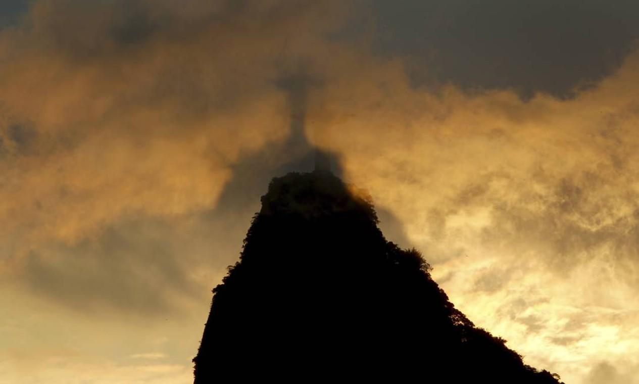 Silhueta do Cristo é vista através de nuvens que cobrem o cume da pedra do Corcovado Foto: Custódio Coimbra / Agência O Globo - 19/12/2017