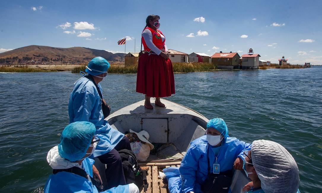 Agentes de saúde do governo peruano durante uma viagem para vacinar moradores das ilhas flutuantes de Uros, no Lago Titicaca, contra a Covid-19 Foto: CARLOS MAMANI / AFP