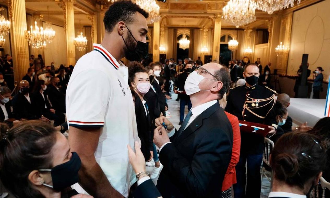 O primeiro-ministro francês, Jean Castex concede o título de Oficial da Ordem do Mérito Nacional ao jogador de basquete francês Rudy Gobert durante a cerimônia de premiação em homenagem aos medalhistas franceses olímpicos e paralímpicos no Tóquio 2021, em Paris Foto: THIBAULT CAMUS / AFP