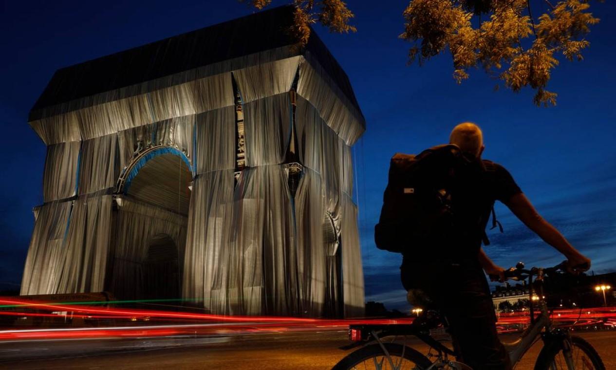 Ciclista olha para o Arco do Triunfo, em Paris, envolto em tecido prata-azul desenhado pelo saudoso artista Christo Foto: GEOFFROY VAN DER HASSELT / AFP