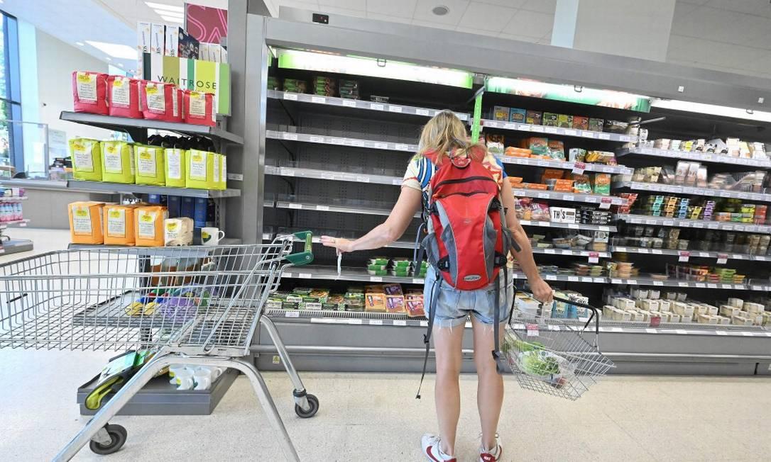 Freguesa observa pratelerias vazias em seção refrigerada de mercado da rede Waitrose, em Londres Foto: JUSTIN TALLIS / AFP/7-9-21