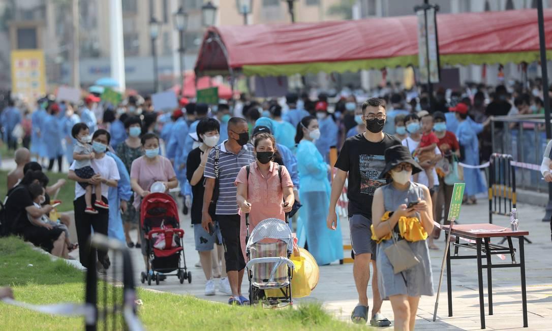 Pessoas caminham em meio a tendas para testagem em massa e bloqueios sanitários em Xiamen, na província de Fujian, na China Foto: STR / AFP