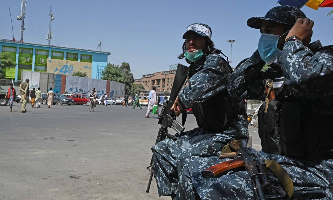 Usando uniformes das antigas forças de segurança afegãs, milicianos do Talibã patrulham rua de Cabul Foto: AAMIR QURESHI / AFP