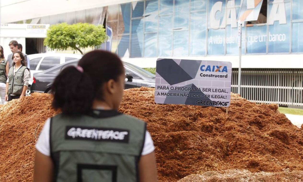 Ativistas do Greenpeace despejaram duas toneladas de pó de serra em frente à sede da Caixa Econômica Federal, em Brasília, para protestar contra financiamento de programas que, segundo a ONG, estariam ligados à destruição da Amazônia Foto: Jorge William / Agência O Globo - 18/11/2014