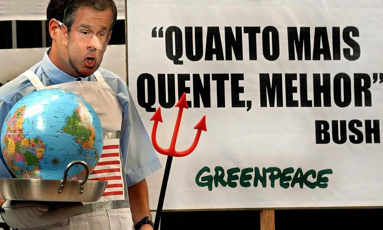 Ativista do Greenpeace, fantasiado de cozinheiro e usando uma máscara do presidente americano George W. Bush, protesta em frente ao consulado dos Estados Unidos, em São Paulo. Bush foi o o único presidente que se recusou a assinar o Protocolo de Kyoto, acordo internacional para a proteção do clima e da camada de ozônio do planeta Foto: Mauricio Lima / AFP - 03/04/2001